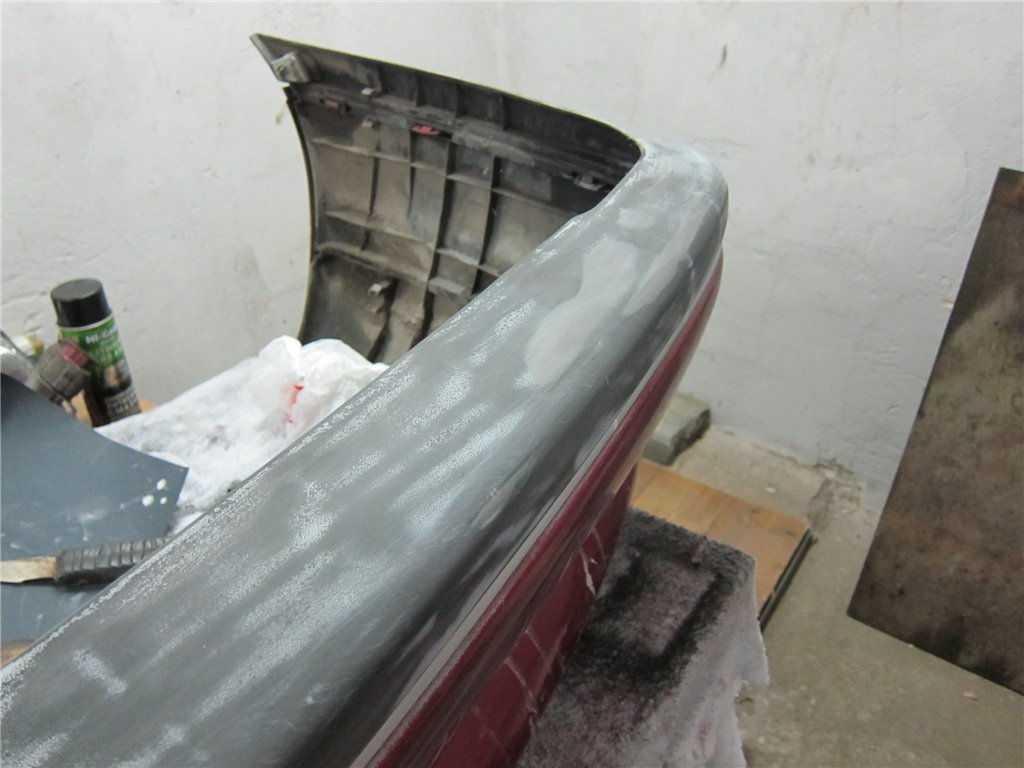 Покрытый грунтом пластиковый бампер автомобиля готов к финишной покраске